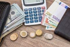 Euro och dollar i handväska med myntet och räknemaskinen Royaltyfri Foto