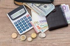 Euro och dollar i handväska med myntet och räknemaskinen Royaltyfri Bild