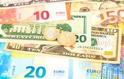 Euro- och dollarmynt som ligger över olik valutasedel Royaltyfri Fotografi