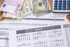 Euro- och dollarräkning-, räknemaskin-, bläckpenna- och myntpengar på kalender Royaltyfri Fotografi