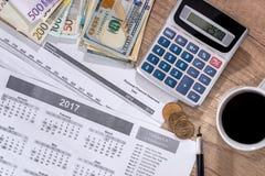 Euro- och dollarräkningar, räknemaskin, bläckpenna och mynt Arkivbilder