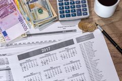 Euro- och dollarräkningräknemaskin, bläckpenna och myntpengar Arkivfoto