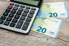 20 euro och en räknemaskin på en trätabell arkivfoto
