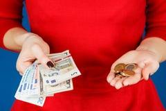 Euro och mynt i händerna av en flicka Arkivfoton