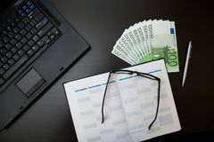 Euro in office. Stack of euro on office desktop with organizer and laptop Royalty Free Stock Photography