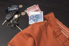 Euro paper money and coins fell out of his pocket on the table, on which lie the keys Royalty Free Stock Photography