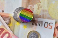 Euro pièce de monnaie avec le drapeau gai sur l'euro fond de billets de banque d'argent Image stock