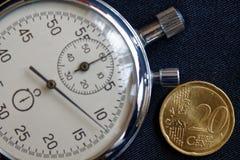 Euro pièce de monnaie avec une dénomination de 20 euro cents et de chronomètre sur le contexte noir de denim - fond d'affaires Image libre de droits