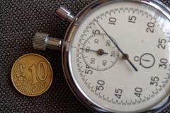 Euro pièce de monnaie avec une dénomination de 10 euro cents et chronomètres sur le contexte brun de denim - fond d'affaires Images stock