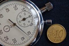 Euro pièce de monnaie avec une dénomination de 10 euro cents et chronomètres sur le contexte noir de denim - fond d'affaires Image libre de droits