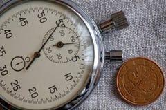 Euro pièce de monnaie avec une dénomination de cinq euro cents (arrière) et de chronomètre sur le contexte blanc de lin - fond d' Photographie stock