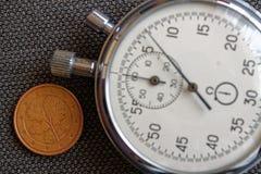 Euro pièce de monnaie avec une dénomination de cinq euro cents (arrière) et de chronomètre sur le contexte brun de denim - fond d Images stock