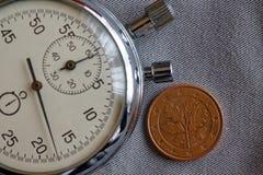 Euro pièce de monnaie avec une dénomination de cinq euro cents (arrière) et de chronomètre sur le contexte gris de denim - fond d Photographie stock
