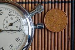Euro pièce de monnaie avec une dénomination de cinq euro cents et de chronomètre sur la table en bois - arrière Photographie stock