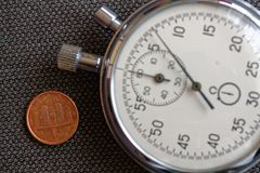 Euro pièce de monnaie avec une dénomination d'un euro cent (arrière) et de chronomètre sur le contexte brun de denim - fond d'aff Photo stock