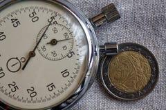Euro pièce de monnaie avec une dénomination de deux euro (arrière) et de chronomètre sur le contexte blanc de lin - fond d'affair Image stock