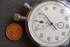 Euro pièce de monnaie avec une dénomination de deux euro cents (arrière) et de chronomètre sur le contexte brun de denim - fond d Photos libres de droits