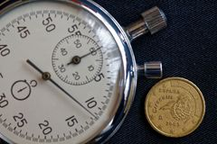 Euro pièce de monnaie avec une dénomination de dix euro cents (arrière) et de chronomètre sur le contexte noir usé de denim - fon Photographie stock