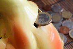 Euro pièce de monnaie avec une dénomination de 1 euro en trou de tirelire, fond de pièces de monnaie Image stock