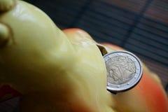 Euro pièce de monnaie avec une dénomination de l'euro deux dans le trou de la tirelire, fond de pièces de monnaie - arrière Photo stock