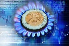 Euro pièce de monnaie sur le brûleur à gaz suggérant le coût de chauffage ou l'évolution naturelle de prix du gaz image stock