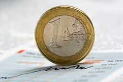 Euro pièce de monnaie sur le graphique de journal - image courante photographie stock libre de droits