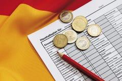 Euro pièces de monnaie avec le crayon et le document sur le drapeau allemand Photos stock