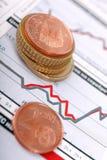 Euro pièces de monnaie et graphique financier. Images stock