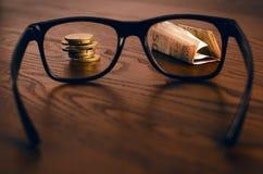 Euro pieniądze monety i papierowy pieniądze skupiali się w szkłach na drewnianym stole Finansowy i biurowy pojęcie Skupiający się Fotografia Stock
