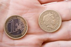 Euro and Pound in Hand. Euro coin and Pound in a hand. Good metaphor for the ongoing debate about the disparity between the currencies and the tug of the Euro on Royalty Free Stock Image