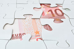 Euro puzzle. Jigsaw puzzle missing pieces reveal euro banknotes Stock Photos