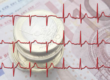 Euro Recovery. Close up of Euro coins overlaid with ECG Graph Stock Photo