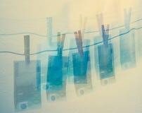 100 euro rekeningen die op clothline het kleurrijke moneylaundring hangen Royalty-vrije Stock Afbeeldingen