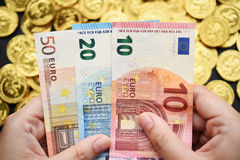 Euro rekeningen op hand met gouden muntstukken Stock Foto