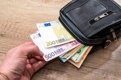 Euro rekeningen op zwarte portefeuille op houten bureau stock foto's