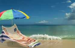 Euro is resting & enjoying on paradise beach. 10 Euro banknote is resting & enjoying on beach chair under colorful umbrella. Tropical beautiful  sea and clouds Stock Photo
