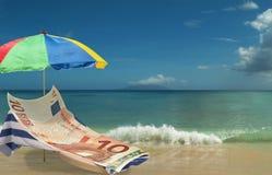 Euro is resting & enjoying on paradise beach. 10 Euro banknote is resting & enjoying on beach chair under colorful umbrella. Tropical beautiful  sea and Stock Photo