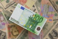 The euro rises above other currency. Hundred euros on a background of other currency, a background not sharp Royalty Free Stock Photo