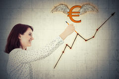 Euro rising graph. Smiling young businesswoman, holding a pencil, drawing winged euro sign and a rising graph on gray wall background. Concept of financial Royalty Free Stock Photo