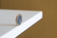 Euro rollt entlang dem Rand der Tabelle Stockfotografie
