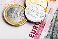 Euro and ruble coins on euro banknotes Stock Image