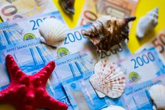 Euro and ruble with red and white seashells on yellow backgrong royalty free stock image