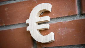Euro- símbolo de madeira no fundo da parede de tijolo Fotos de Stock