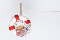 Euro saver. Clothespin fixing a safety buoy with euro banknotes on a clothes line. financial concept for currency risk or protection Royalty Free Stock Image