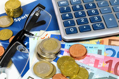 Euro Savings. Euro banknotes with coins, calculator and glasses on a bankbook Royalty Free Stock Photo