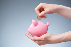 Euro Savings - Coin in a Piggy Bank. A female hand inserting a two Euro coin into a pink piggy bank Stock Photo