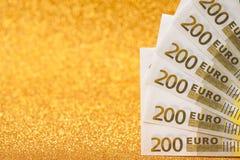200-Euro - Scheine auf goldenem funkelndem Hintergrund Viel Geld, Luxus Lizenzfreies Stockfoto