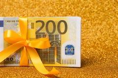 200-Euro - Scheine auf goldenem funkelndem Hintergrund Viel Geld, Luxus Lizenzfreie Stockfotos