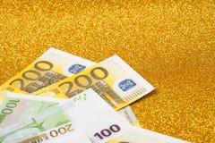 200-Euro - Scheine auf goldenem funkelndem Hintergrund Viel Geld, Luxus Stockbilder