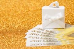 200-Euro - Scheine und Geschenkbox auf goldenem funkelndem Hintergrund Lizenzfreie Stockbilder